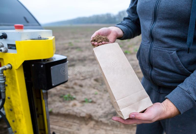 Soil Sampling. An engineer employee of a research laboratory packs a soil sample in a paper package. Automated probe for soil royalty free stock photography