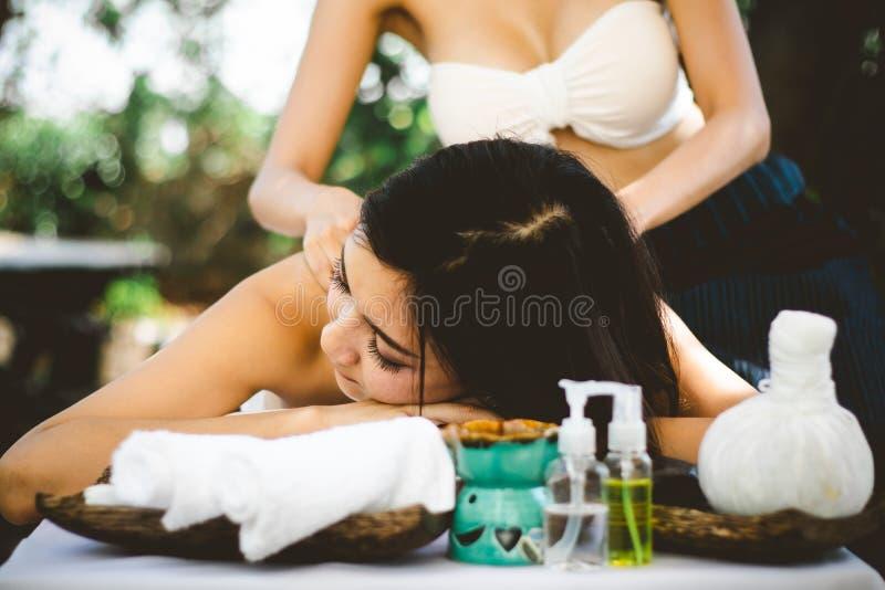 Soin de fuselage Jeune femme asiatique ayant le massage avec les boules de fines herbes chaudes pour la relaxation profonde, photos stock