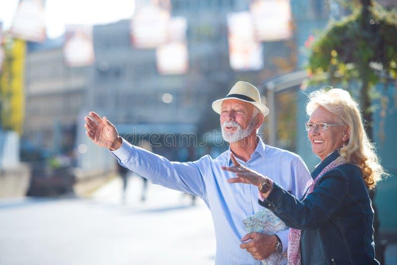 Soin de la ville nouvelle Intégral du vieil homme et de la femme optimistes se tiennent près de la route et essayent d'attraper l photo libre de droits