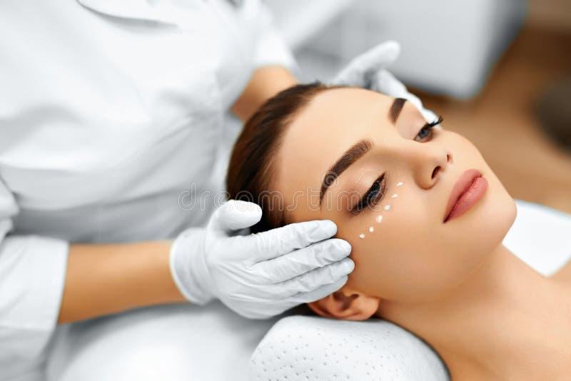 Soin de peau Crème cosmétique sur le visage de la femme Demande de règlement de station thermale de beauté image libre de droits