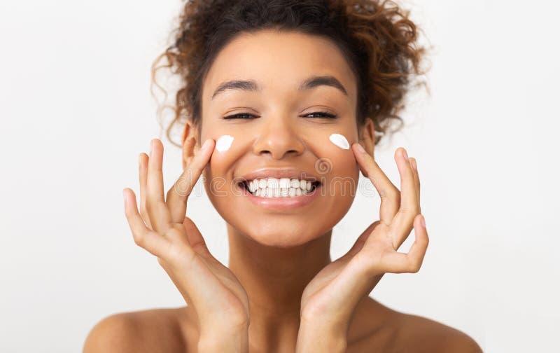 Soin de peau Femme d'Afro appliquant la crème cosmétique sur son visage photos stock