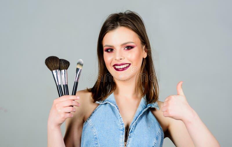 Soin de peau Regard bon et se sentir s?r Femme appliquant la brosse de maquillage Approvisionnements professionnels de maquillage images stock