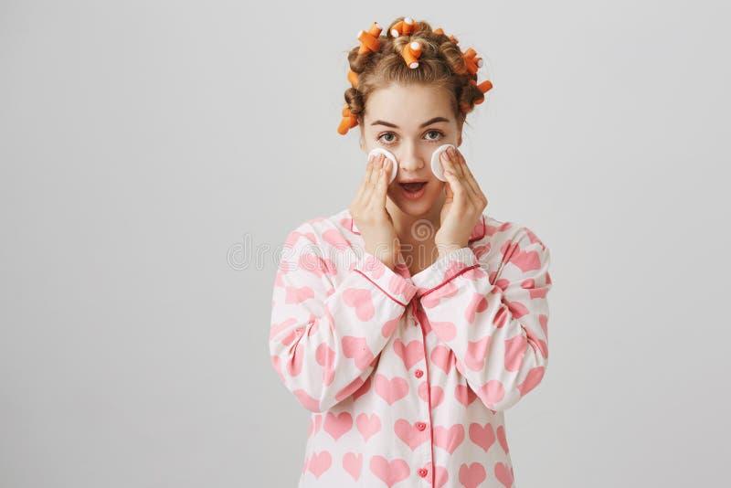 Soin de visage et concept de beauté Fille fascinante mignonne avec des bigoudis de cheveux essuyant la peau avec la protection de photographie stock
