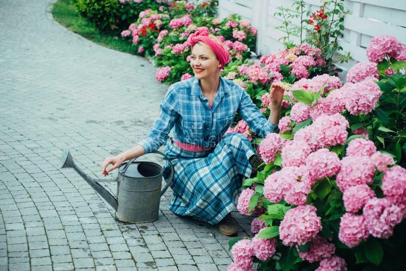 Soin et arrosage de fleur sols et engrais jardinière heureuse de femme avec des fleurs soin de femme des fleurs dans le jardin image stock