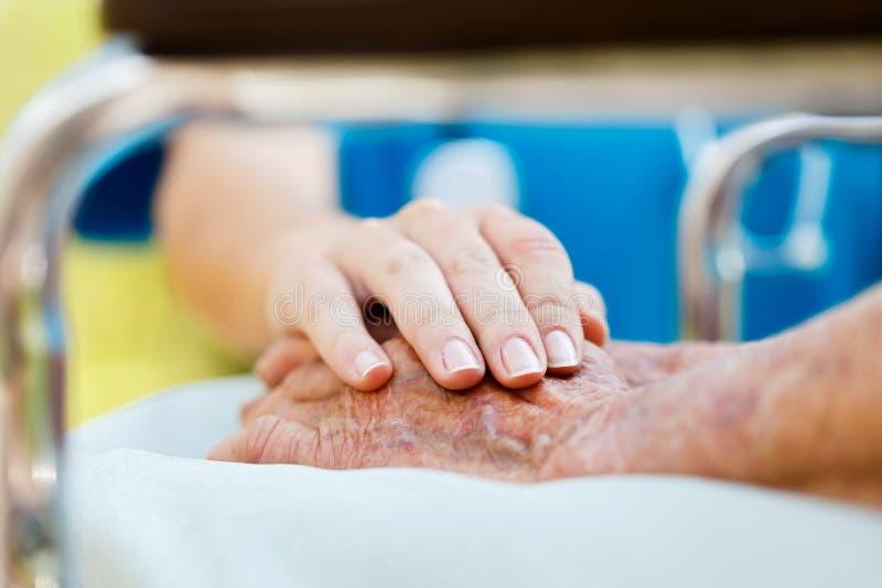 Soin pour des personnes âgées dans le fauteuil roulant images libres de droits