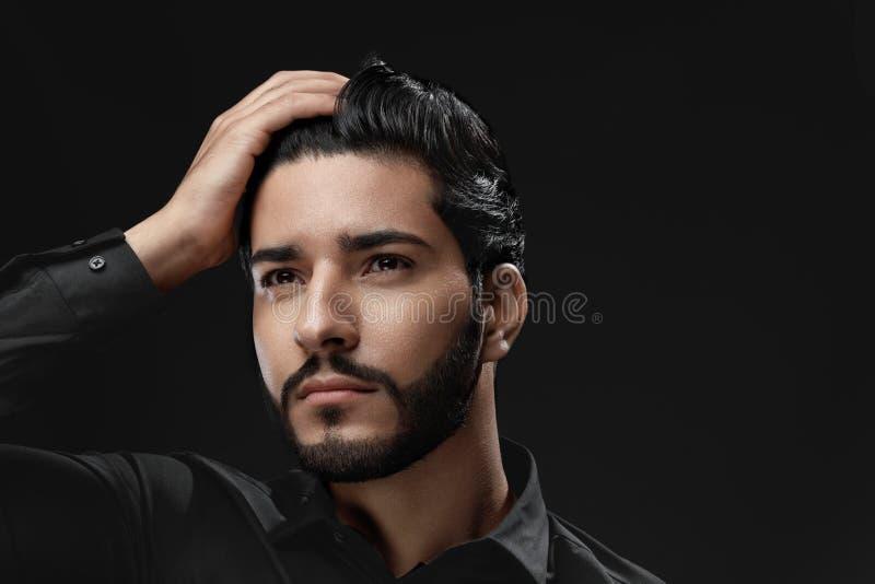 Soins capillaires d'hommes Homme avec la barbe, cheveux noirs émouvants de visage de beauté photos stock