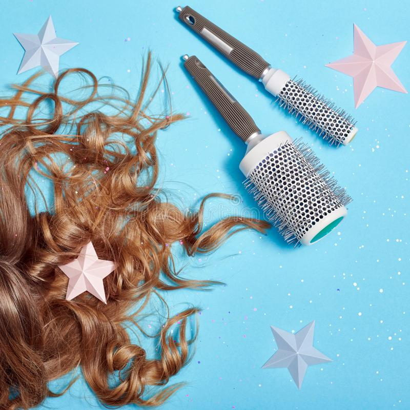Soins capillaires, longs beaux cheveux et peigne, peignant, racines saines fortes Cheveux se trouvant sur le fond bleu Coiffeur e photos stock
