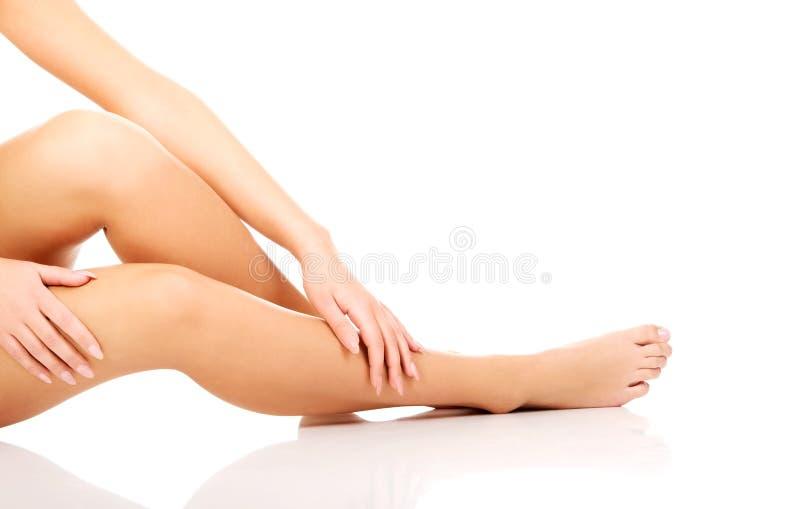 Soins de femme au sujet de ses jambes image stock
