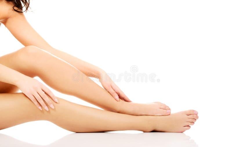 Soins de femme au sujet de ses jambes photographie stock libre de droits