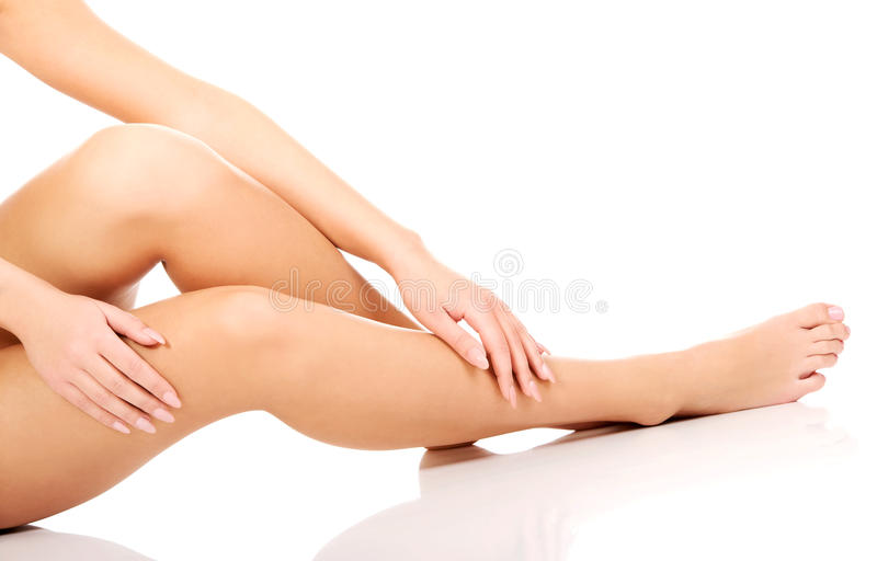 Soins de femme au sujet de ses jambes photo stock