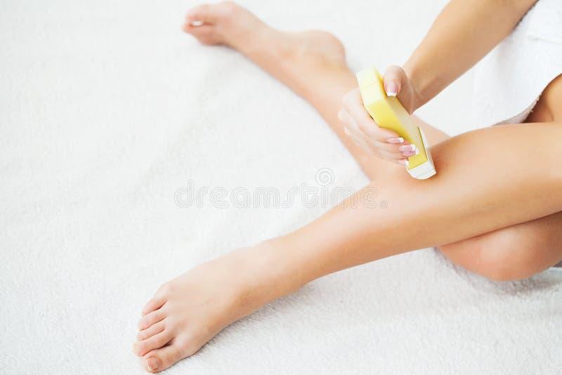 Soins de la peau et santé Épilation Jeune femme d'ajustement cirant ses jambes avec de la cire dépilatoire Heater For de gaine à  photographie stock