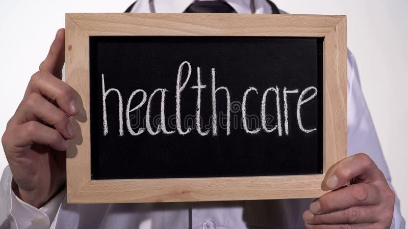 Soins de santé écrits sur le tableau noir dans des mains de thérapeute, service médical, hôpital image libre de droits