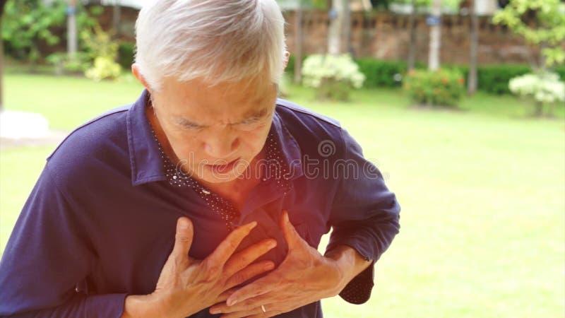 Soins de santé asiatiques de course de crise cardiaque de douleur thoracique d'homme supérieur images libres de droits
