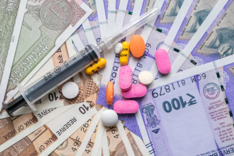 Soins de santé en Inde - concept de la santé et des affaires montrant les notes indiennes de devise de papier, pilules, seringue images libres de droits