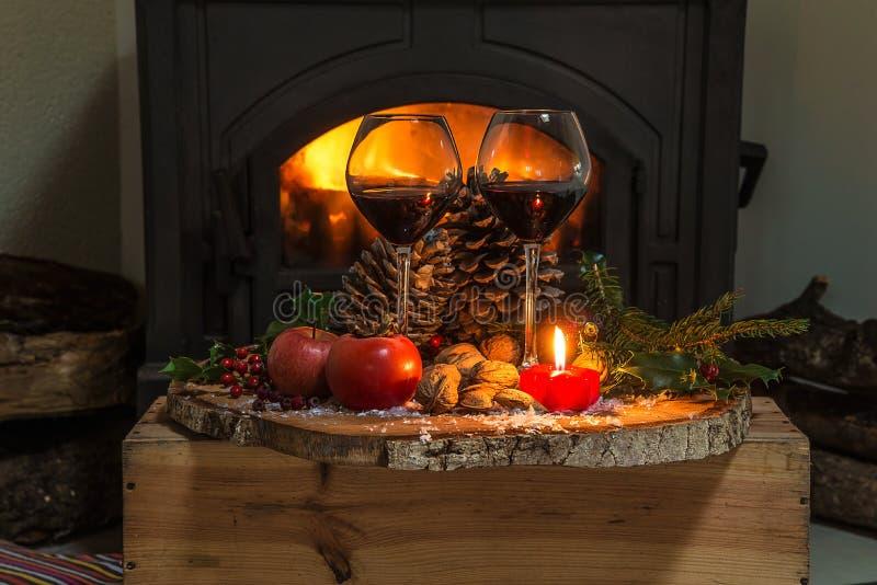 Soirée confortable de Noël ou d'hiver : deux verres du vin rouge et de la cheminée de vintge photographie stock