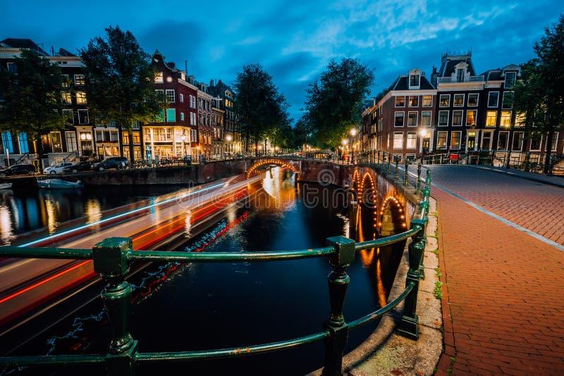 Soirée dans la ville d'Amsterdam, les traînées légères et les réflexions sur l'eau aux canaux de Leidsegracht et de Keizersgracht photo stock
