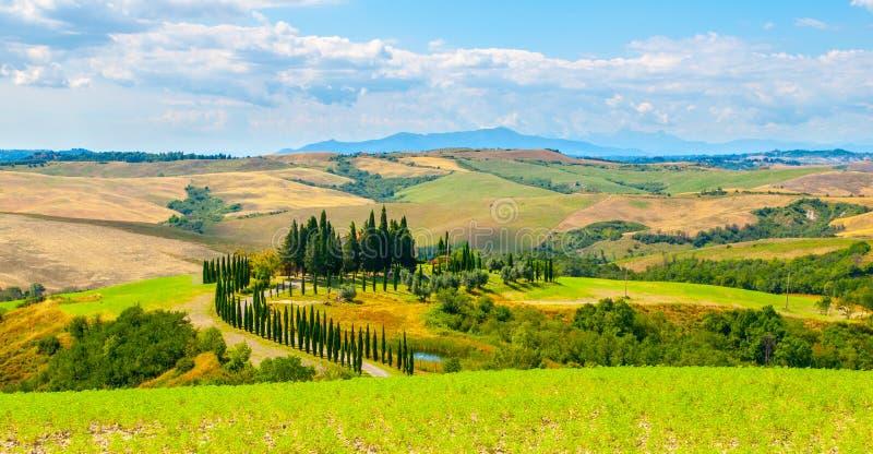 Soirée en Toscane Paysage de Hilly Tuscan avec l'allée d'arbres de cyprès et la maison de ferme, Italie image libre de droits
