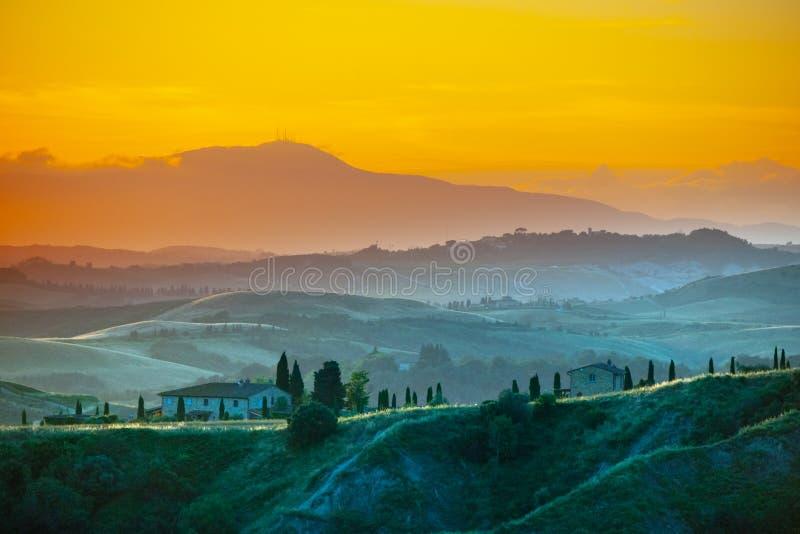 Soirée en Toscane Paysage de Hilly Tuscan dans l'humeur d'or au temps de coucher du soleil avec des silhouettes des cyprès et des photos libres de droits