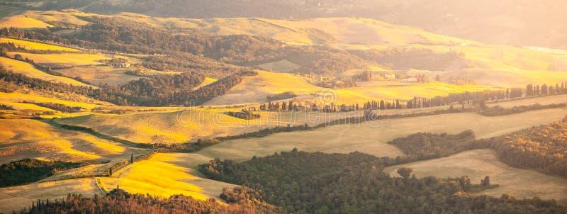 Soirée en Toscane Paysage de Hilly Tuscan dans l'humeur d'or au temps de coucher du soleil avec des silhouettes des cyprès et des photo libre de droits