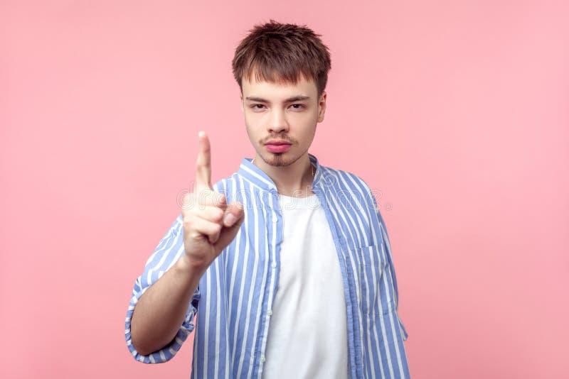 Sois prudent ! Portrait d'un homme aux cheveux bruns bosseux avec petite barbe et moustache montrant un signe d'avertissement, la photo libre de droits