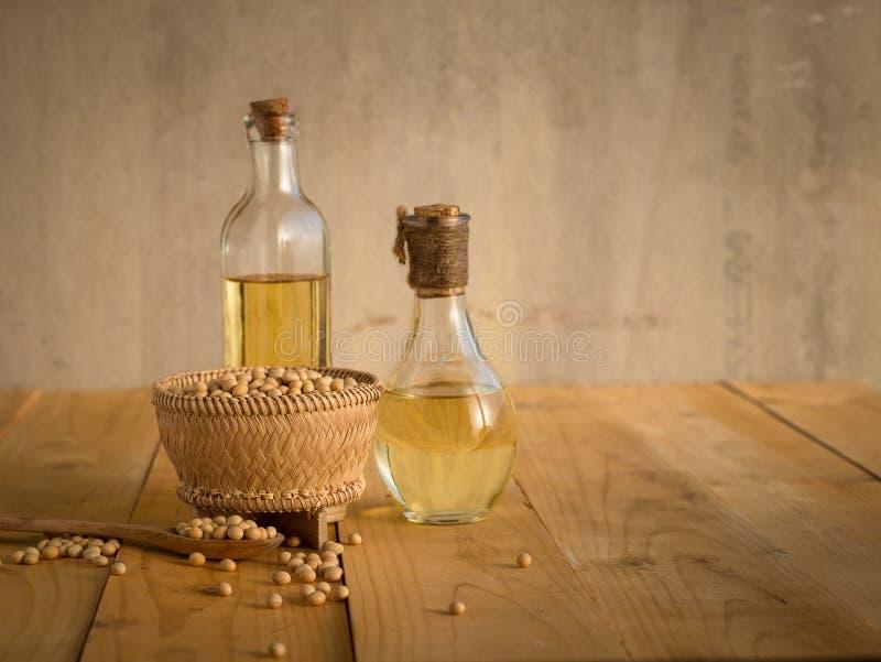 Sojabönabönan och sojabönor oljer på en trätabell royaltyfria bilder