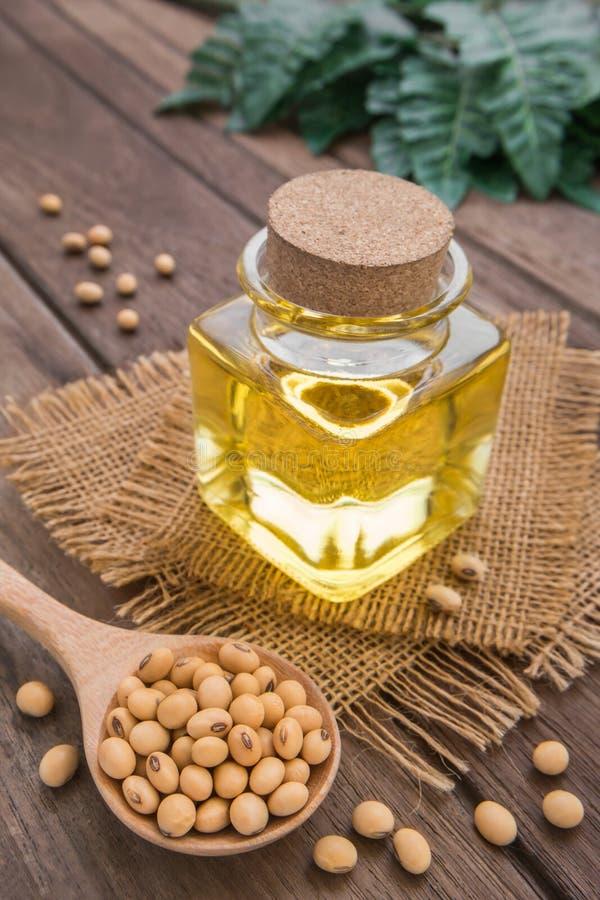 Sojabönabönan och sojabönor oljer på trätabellen royaltyfria bilder