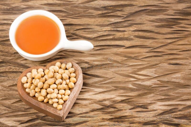 Sojabönabönan och sojabönor oljer på trätabellen - maximal Glycine arkivbilder