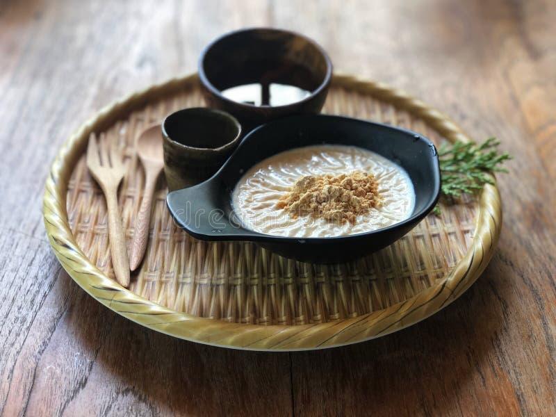 Sojapudding in de zwarte kop die met bruine suiker en suikerstroop wordt bedekt en hete thee op bamboedienblad royalty-vrije stock foto's