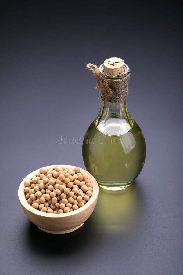 Sojas en un aceite de madera del cuenco y de soja en un fondo negro fotografía de archivo libre de regalías