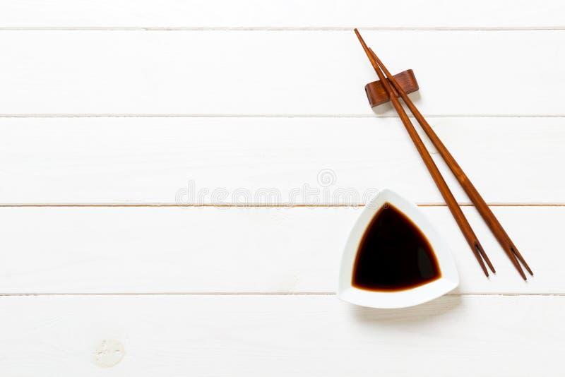 Sojasaus met eetstokjes op witte houten lijstachtergrond stock fotografie