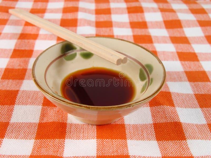 Sojasoße und Ess-Stäbchen auf einer Haupttabelle lizenzfreies stockbild