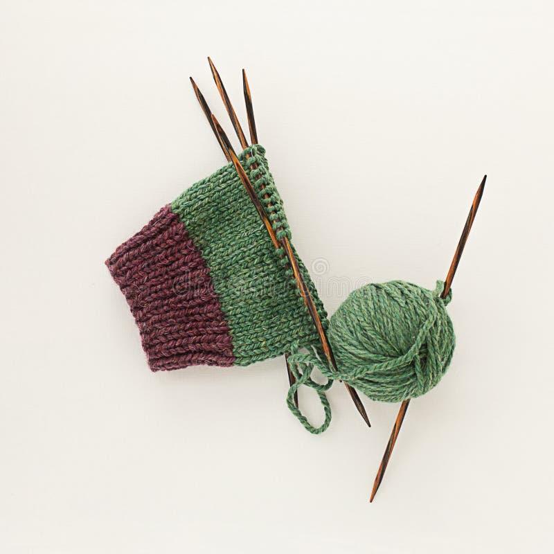 Sokken groene pluizige wollen gebreide breinaalden op lichte bedelaars royalty-vrije stock foto