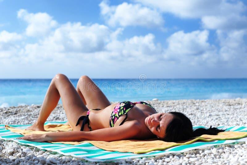 Sol atractivo del gril que broncea en una playa tropical imagenes de archivo