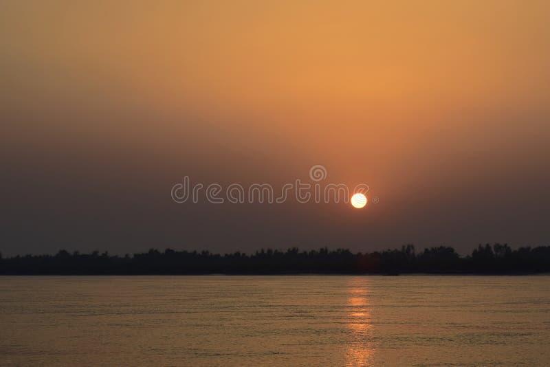 Sol bajo de la puesta del sol en cielo anaranjado en el río Assam en la India fotografía de archivo libre de regalías