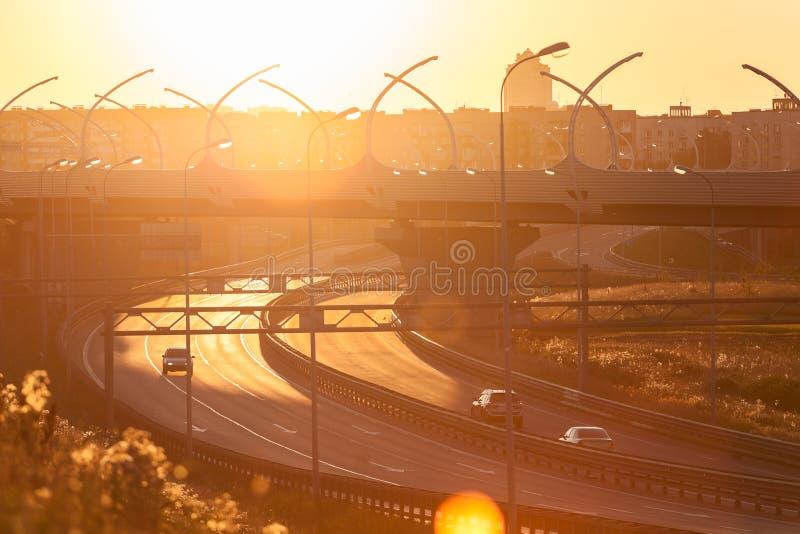 Sol brilhante do por do sol sobre a junção da estrada, condução de carros na estrada imagem de stock royalty free