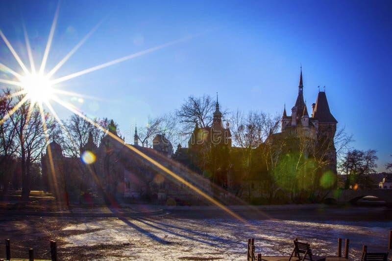Sol brillante con los rayos que brillan en cielo azul claro sobre el castillo de Vajdahunyad y el lago congelado con la pista de  foto de archivo