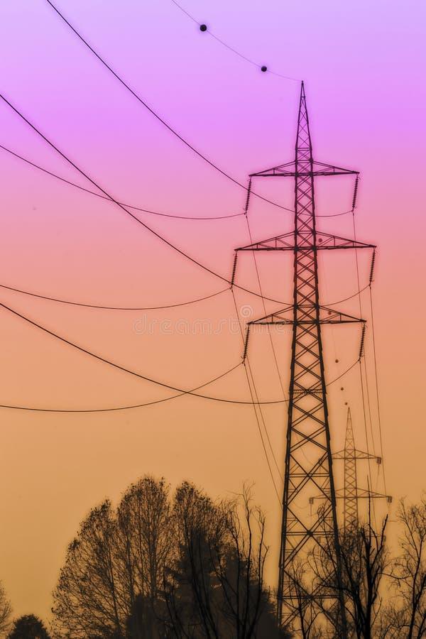 Sol cor de laranja rosa com postes de alta tensão imagem de stock
