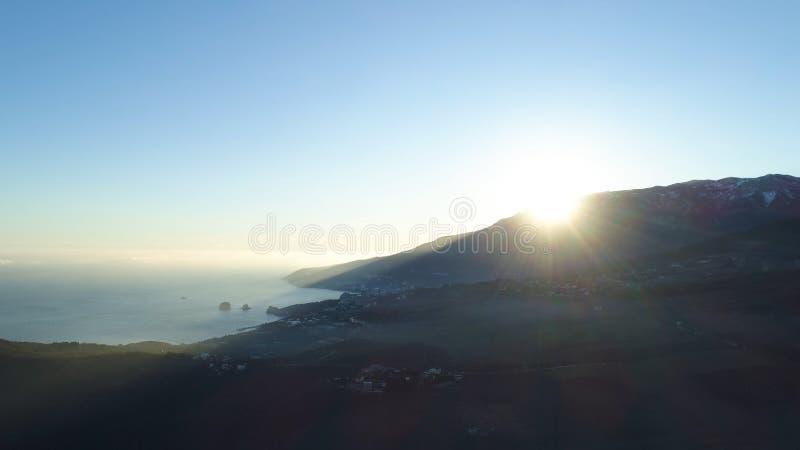Sol da manhã que aumenta sobre uma montanha perto do mar no fundo do céu azul, beleza da natureza tiro Nascer do sol pitoresco em fotos de stock