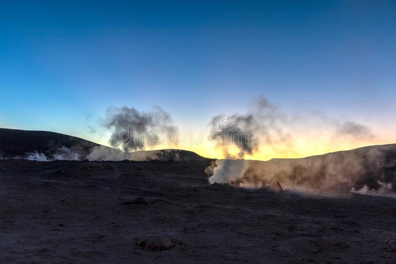 Sol de la马纳娜,朝阳通入蒸汽的喷泉领域高在玻利维亚人阿尔蒂普拉诺高原,玻利维亚的一个巨型的火山口 图库摄影
