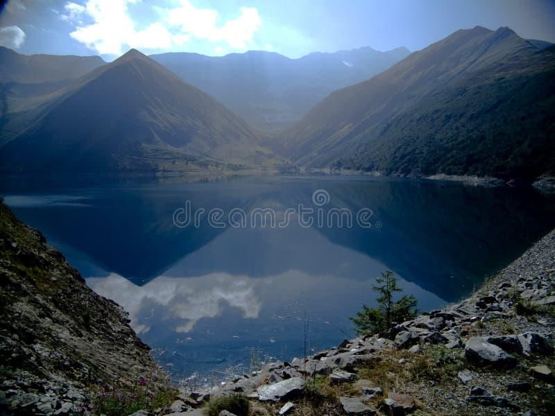 Sol de la mañana en un lago en las montañas francesas foto de archivo