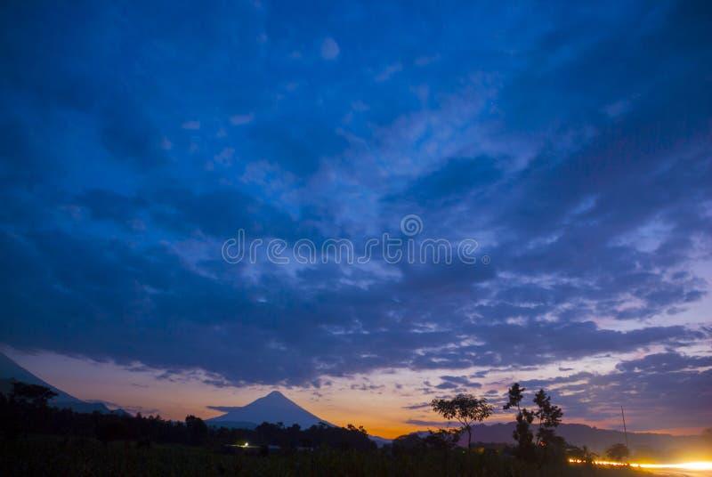 Sol de nivelamento dram?tico na estrada e no vulc?o na Guatemala, Am?rica Central fotografia de stock royalty free