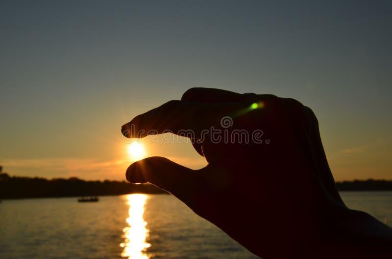 Sol de travamento da mão da jovem mulher entre os dedos durante o por do sol fotos de stock royalty free