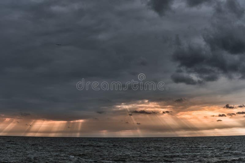 Sol`en s rays bortgång till och med stormmolnen över havet Liepaja Lettland arkivfoton