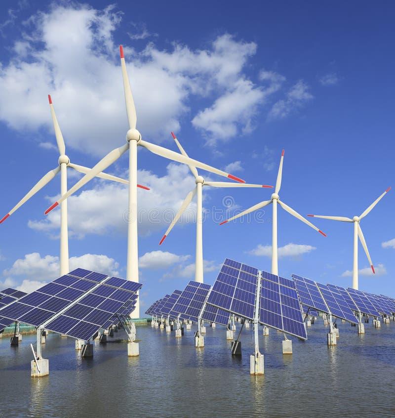 Sol- energipaneler och windturbin royaltyfria foton