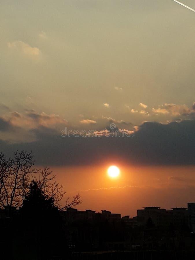 Sol för stad för solnedgångmolnhimmel fotografering för bildbyråer