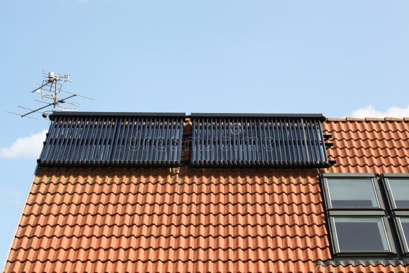 Sol- för varmvattenpanel för glass rör samling på ett tak royaltyfri bild