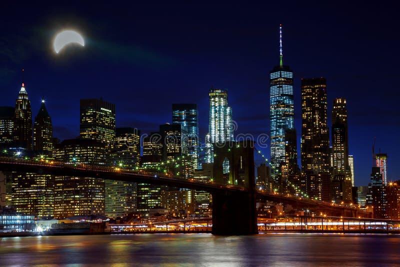 Sol- förmörkelse, New York NY august 21 2017 New York City & x27; upplyst bro- och Manhattan för s Brooklyn horisont fotografering för bildbyråer