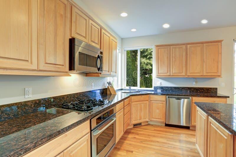 Sol fyllt gourmet- kök med träcabinetry royaltyfria foton