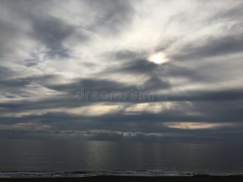 Sol i molnen som reflekterar i havet fotografering för bildbyråer