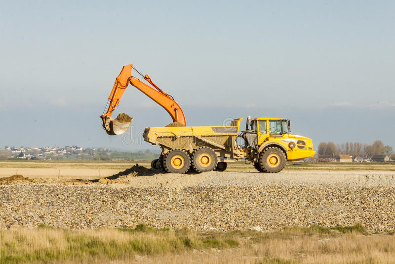 Sol jaune de chargement d'excavatrice sur un camion au mien. photographie stock